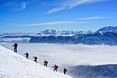 Group of persons back-country skiing ascending towards Sonntagshorn, Berchtesgaden range in background, Sonntagshorn, Chiemgau range, Salzburg, Austria
