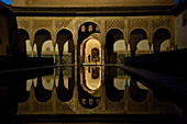 Fine Moorish wall decorations in the Nasrid palace in the Alhambra, reflections in a pool, night visit, Granada, Andalusia, Spain, Europe