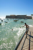 Boats on the sea and a boy going to jump from the harbour wall into the sea next to the Castillo de Santa Catalina, Cadiz, Andalusia, Spain, Europe
