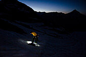In the light of her headlamp, a female alpinist is putting on her crampons on the Hohlaub Glacier, in the background the first light of dawn, Pennine Alps, canton of Valais, Switzerland