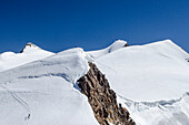 Two mountaineers standing on the summit of the Ludwigshoehe, behind them four persons climbing Parrotspitze, in the background the summit of Signalkuppe or Punta Gnifetti with the Margherita Hut on top, Monte Rosa massif, Pennine Alps, canton of Valais, S