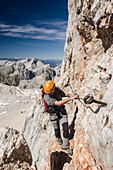 An alpine hiker or climber on the upper part of the ferrata called Bamberger Weg leading to the summit of the Triglav, Julian Alps, Slovenia
