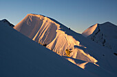 Two alpinists on the summit ridge of Roccia Nera, one of the five summits of the Breithorn massif, above them big cornices in the morning sun, behind them the summit of Castor, Valais Alps, canton of Valais and region of Aosta Valley, national border of S