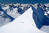 Two groups of hikers on snowshoes during their ascent of the Pigne d'Arolla, in the background the summits of the western Pennine Alps, canton of Valais, Switzerland