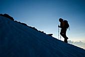 Eine Bergsteigerin früh morgens auf dem Südgrat des Weissmies, Walliser Alpen, Kanton Wallis, Schweiz
