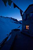 Im Stubenfenster der Bächlitalhütte brennt Licht, während es draussen dämmert und der Mond scheint, Bächlital, Grimselgebiet, Berner Alpen, Kanton Bern, Schweiz
