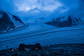 The Concordia Hut while night is falling, sitting high above the large flat space called Concordia, where major arms of the Great Aletsch Glacier converge, Bernese Alps, canton of Valais, Switzerland