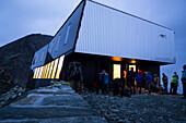 Früh morgens bereiten sich Gäste vor der neuen, modernen Hütte namens Cabane de Tracuit für die Tour aufs Bishorn vor, während die Fenster der Hütte in der Morgendämmerung leuchten, Val d'Anniviers, Walliser Alpen, Kanton Wallis, Schweiz