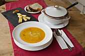 An antique soup bowl, a soup bowl filled with pumpkin soup and a small cheese platter in Hotel Ofenhorn in the village of Binn, canton of Valais, Switzerland