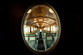 View through a decorated door window into one of the historic wagons of the Golden Pass Railway travelling on the Montreux-Bernese Oberland railway, cantons of Vaud and Bern, Switzerland