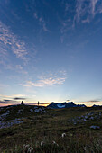 Früh morgens geht eine Person auf den Steinmann auf dem Karstgipfel namens Silberen zu, dahinter die Gipfel des Glärnisch Massivs, Glarner Alpen, Kantone Schwyz und Glarus, Schweiz