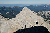 A hiker standing on the shoulder of Triglav, behind in the middle of the picture Mount Rjavina, Julian Alps, Slovenia
