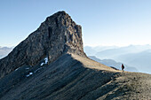 A young man hiking over trackless terrain towards the summit of Felsberger Calanda, massif of Calanda, Grison Alps, cantons of Grison and St. Gallen, Switzerland