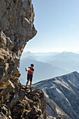 A young alpine hiker looking for a possible scrambling route to reach the summit of Felsberger Calanda, massif of Calanda, Grison Alps, cantons of Grison and St. Gallen, Switzerland