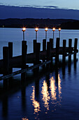 Torches on a pier, Fraueninsel, Chiemsee, Bavaria, Germany