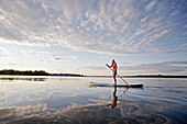 Woman stand up paddling on lake Chiemsee, Chiemgau, Bavaria, Germany