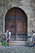 Female cyclist sitting in front of an old door, Chiemgau, Bavaria, Germany