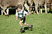 Boy wearing traditionl clothes running over a meadow, Viehscheid, Allgau, Bavaria, Germany