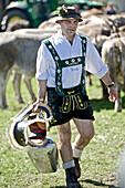 Man wearing traditional clothes carrying a cow bell, Viehscheid, Allgau, Bavaria, Germany