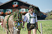 Man wearing traditional clothes with a decorated cattle, Viehscheid, Allgau, Bavaria, Germany