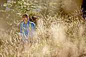 Young man hiking up a mountain on a sunny day, Oberstdorf, Bavaria, Germany
