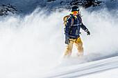 Young female snowboarder riding through deep powder snow in the mountains, Pitztal, Tyrol, Austria