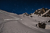 Ski-tourers in the light of the full-moon (ascent- and descent-tracks) close to the Grialetsch hut, Grisons, Switzerland, Europe
