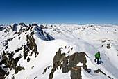 A mountaineer close to the summit of Piz Sarsura (3178 m), in the background Grialetschhut with Piz Radoent and Schwarzhorn, summits on the horizon (from left to right): Piz Vadret, Titlis, Toedi, Clariden, Buendner Vorab, Ringelspitz, Pizol, Hochfinsler,