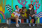 Daughter, dog and mother on bench in front of wall mural, Montevideo, Montevideo, Uruguay