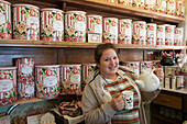Cheerful woman pours tea at La Cabaña Casa de Te tea house, Ushuaia, Tierra del Fuego, Patagonia, Argentina