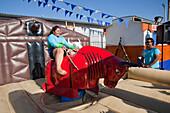 Young woman enjoys bull riding at amusement park, Coquimbo, Coquimbo, Chile