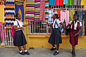 Teenage girls in school uniforms share a laugh, Port Antonio, Portland, Jamaica