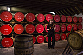 Friendly tour guide Kathryn in front of whisky ageing barrels at The Glenmorangie Whisky Distillery, Tain, Ross-shire, Highland, Scotland, United Kingdom