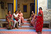Cheerful women in colorful dresses outside school building, Porbandar, Gujarat, India