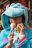 Young girl in animal costume with ice cream cone and smartphone, Shanghai, China