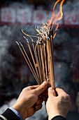 Hands hold incense during worship at Jade Buddha Temple, Shanghai, China