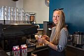 Pretty barista prepares delicious cappuccino at Kaffemisjonen cafe, Bergen, Hordaland, Norway