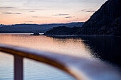 Railing of cruise ship MS Deutschland (Reederei Peter Deilmann) and fjord landscape at dusk, near Bergen, Hordaland, Norway