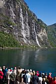 Passengers on deck cruise ship MS Deutschland (Reederei Peter Deilmann) admire Seven Sisters Waterfall in Geirangerfjord, Geiranger, More og Romsdal, Norway