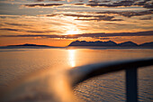 Deck railing of cruise ship MS Deutschland (Reederei Peter Deilmann) with coastline and mountains at sunset, near Lofoten, Norway
