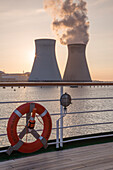 Lifering and railing of cruise ship MS Deutschland (Reederei Peter Deilmann) with Doel Nuclear Power Station on Scheldt river at sunset, near Antwerp, Flemish Region, Belgium