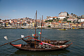 Traditional port wine transport boats on Douro river with view of Ribeira old town and historical center, Vila Nova de Gaia, Porto, Norte, Portugal