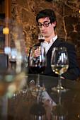 Man holds glass of port during port wine tasting at Burmester winery, Vila Nova de Gaia, Porto, Norte, Portugal
