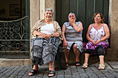 Three elderly women sit in alley and laugh heartily in Ribeira old town and historical center, Porto, Norte, Portugal
