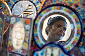 Reflection of young woman in ornamental glassware mirror, Seville, Andalusia, Spain