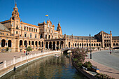 People row boats on canal at Plaza de Espana in Maria Luisa Park, Seville, Andalusia, Spain