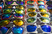 Reflection of palm trees in colorful (fake) Ray-Ban sunglasses for sale by street vendor, Alicante, Andalusia, Spain