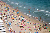 People enjoy a sunny afternoon at Playa del Postiguet beach, Alicante, Andalusia, Spain