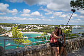 Two young women take selfie photograph overlooking Cala Galdana bay and beach with smartphone on extension stick, Cala Galdana, Menorca, Balearic Islands, Spain