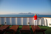 Woman stands at railing of cruise ship MS Deutschland (Reederei Peter Deilmann) and looks towards Tunisian coastline, near La Goulette, Tunis, Tunisia